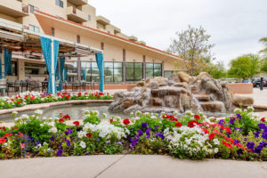 The exterior of the Friendship Village senior living center including red, white, and purple flowers and a natural rock landscape fountain