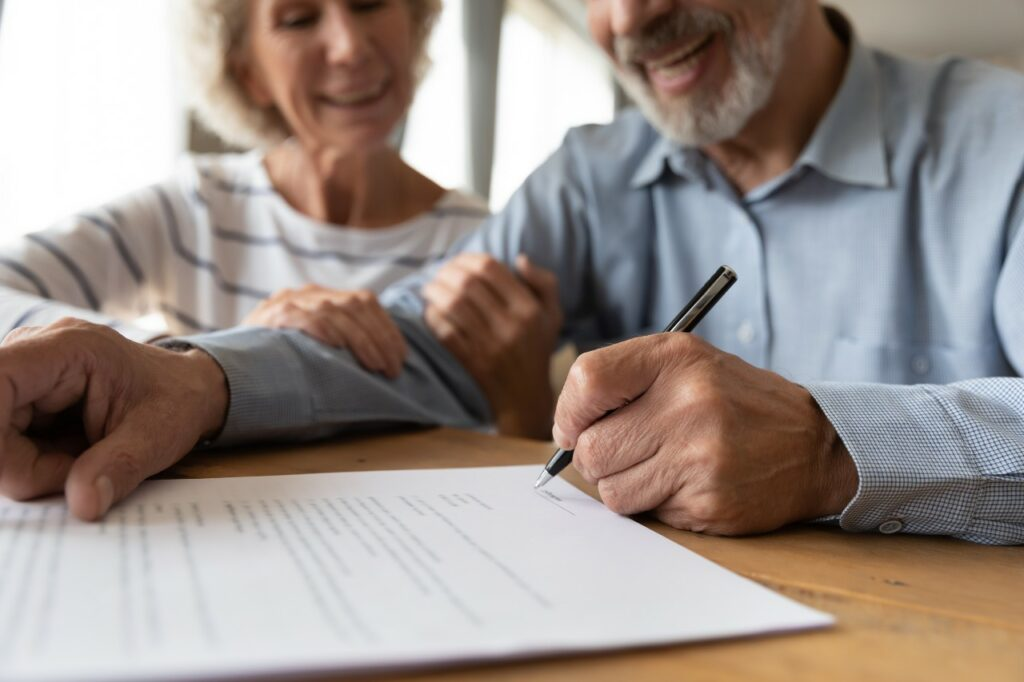 A senior man signs a contract while a senior woman sits next to him