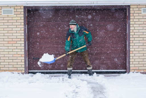 older adult smiling as he shovels snow off his driveway