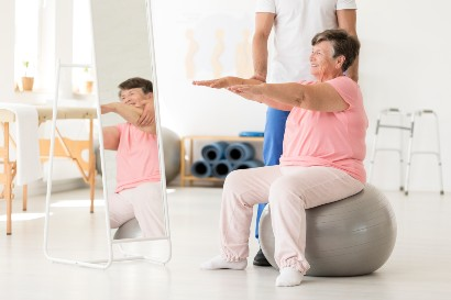 senior exercising with a fitness instructor in a senior living community