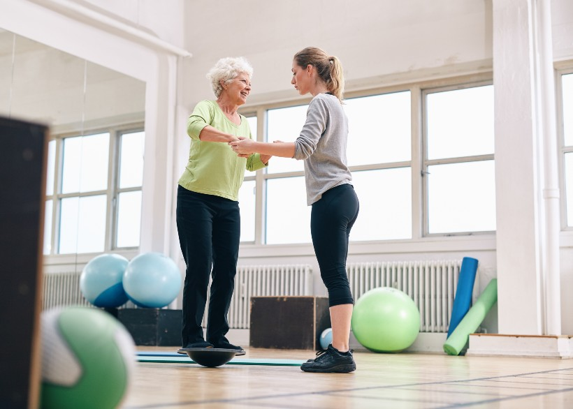 fitness instructor assisting a senior living resident while exercising