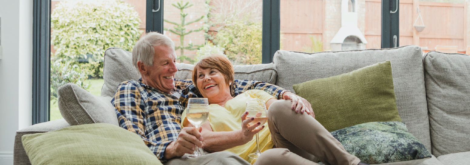 Senior couple laying on a couch enjoying wine