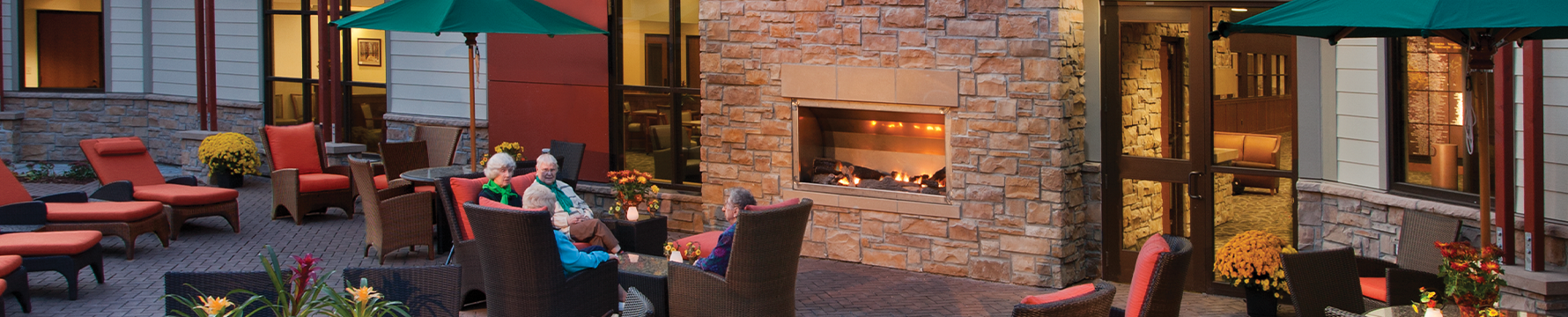 An outdoor sitting area with a fireplace at Friendship Village of Bloomington senior living community
