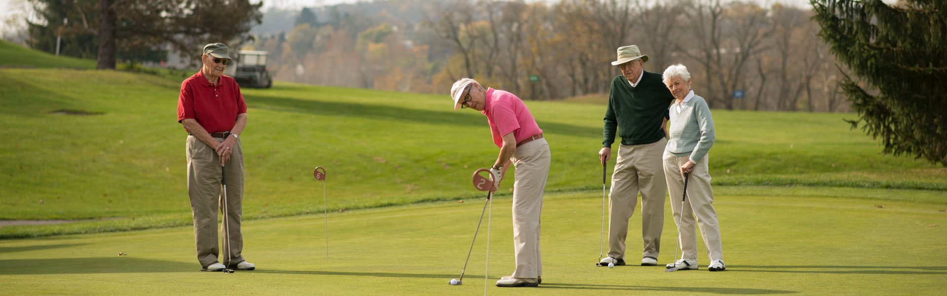 A group of seniors playing golf on the golf course at their senior living community