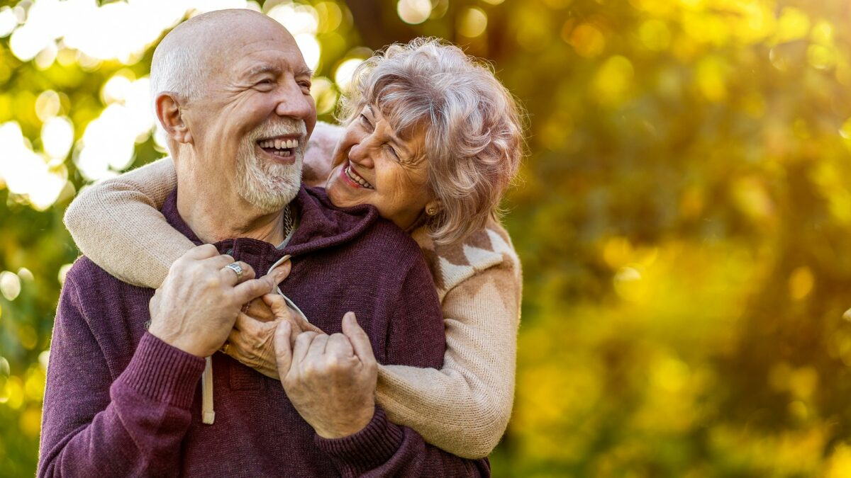 Senior couple smiling outside.