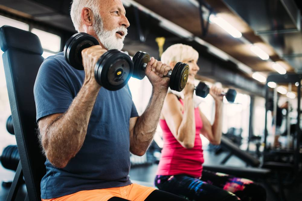 a senior couple working out in a gym by lifting weights
