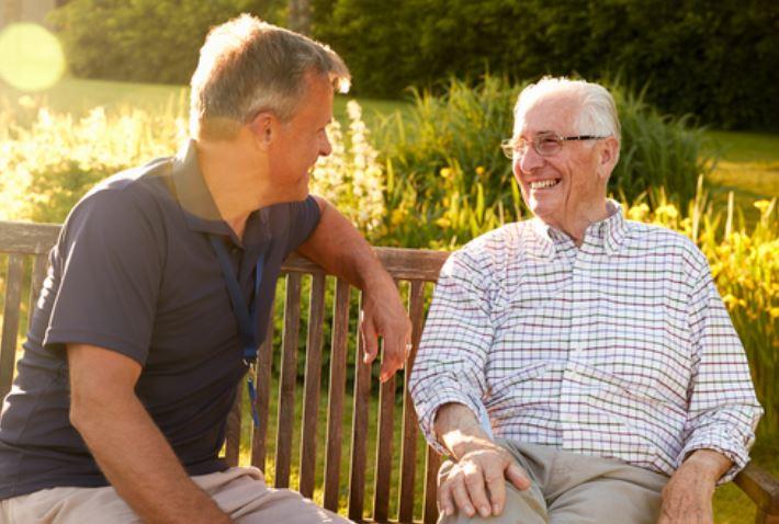 Two senior men sitting on a bench laughing