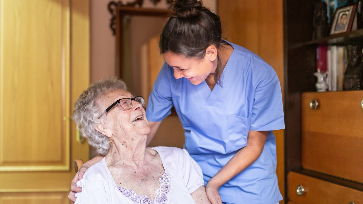 Senior woman and home care nurse laughing together.