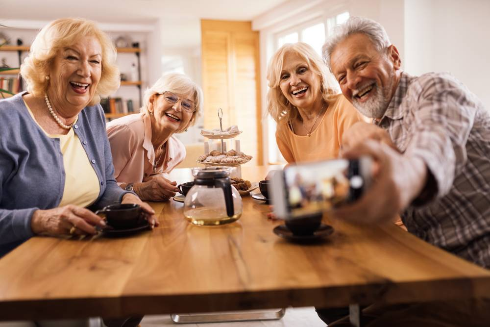 A group of independent living residents taking a selfie at the kitchen table