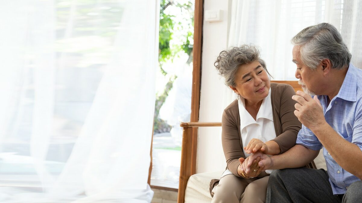 Senior couple talking together on couch, man looks disoriented.