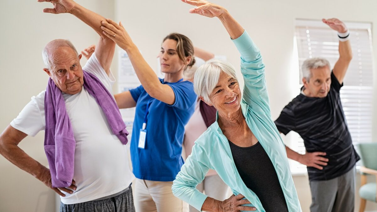 Group of seniors taking an exercise class in a senior living facility.