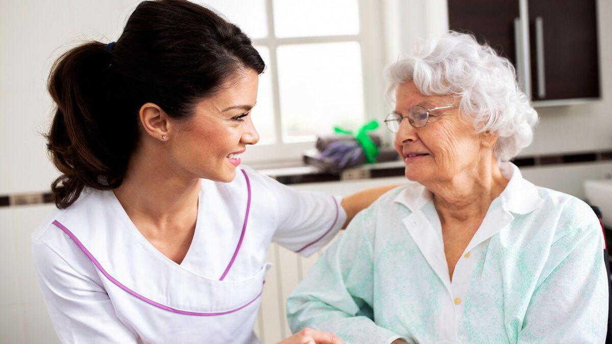 Senior woman speaking with caregiver or nurse.