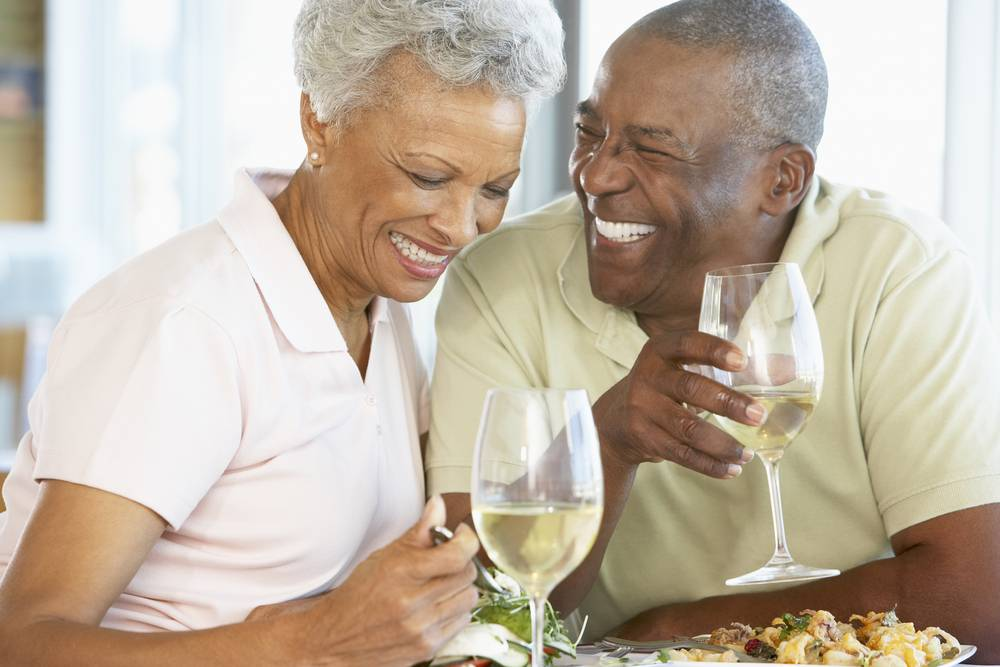 senior couple laughing while eating and drinking white wine