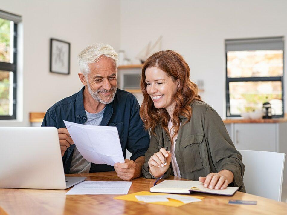 Senior couple reviews their finances at home.