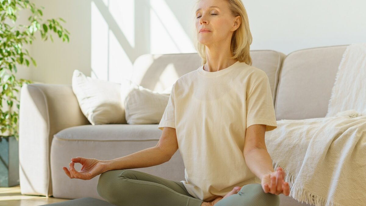 Senior woman doing lotus position and practicing wellness.