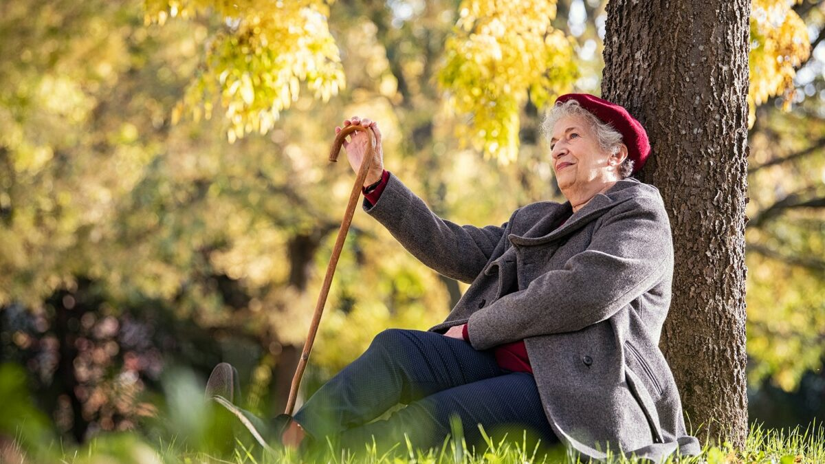 Senior woman sitting and relaxing under a tree in a park.