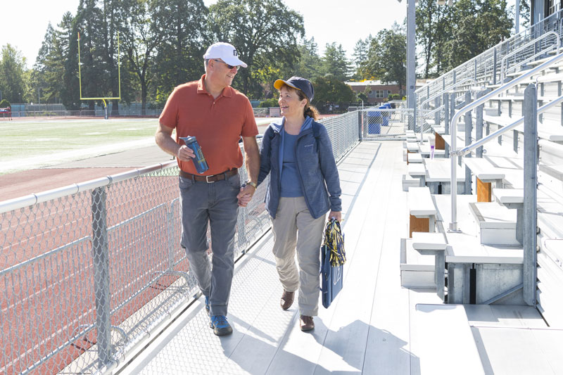 Two senior walk into nearby George Fox University Football Stadium