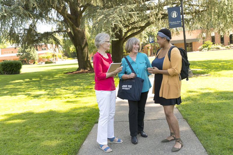 Two senior women stop to talk to a female college student at George Fox University