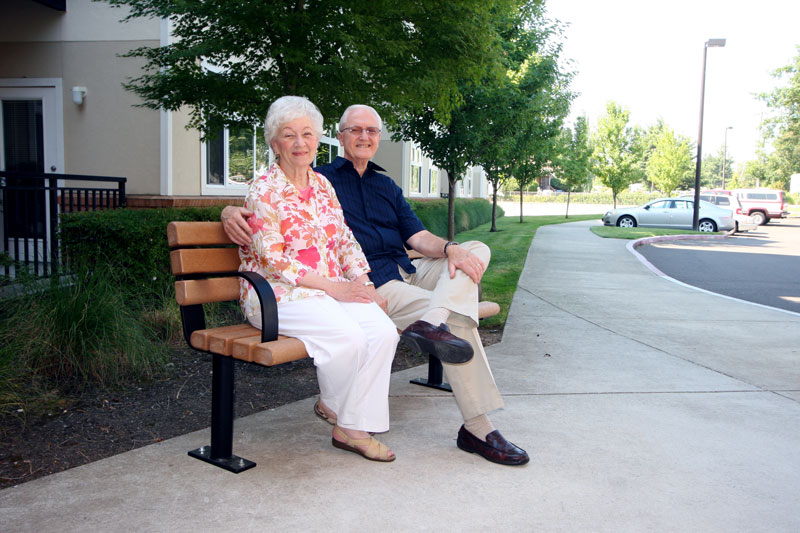 Two seniors pose for a photo on a park bench