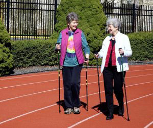 Two senior woman walking the running track