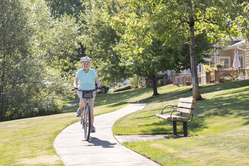 A senior rides their bike on the paved paths in Friendsview
