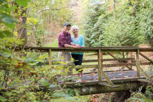 A senior couple poses for a photo on a wood bridge