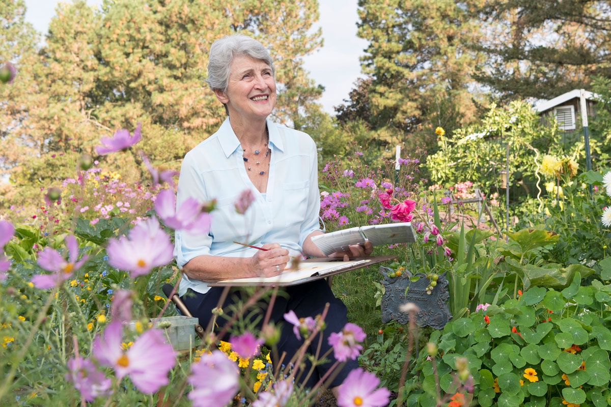 Senior woman painting in the garden
