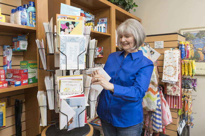 A senior woman looks through greeting cards in the Friendsview shop