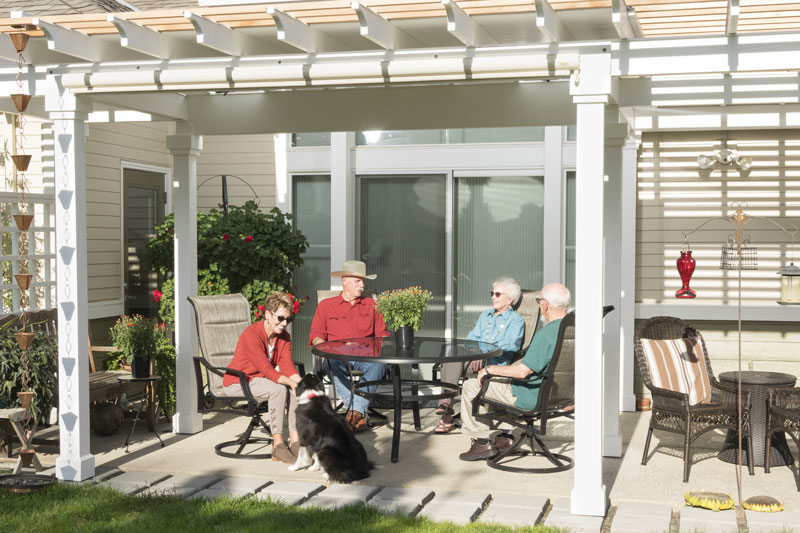 Two senior couples sit outside with a dog on the patio