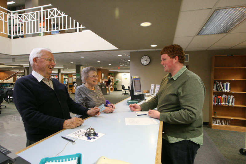 Two seniors talk with the librarian at George Fox University