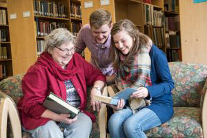 A senior woman sits with two college students and looks at books in the library
