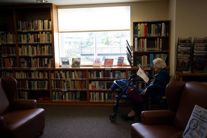 A senior woman reading a magazine in the library