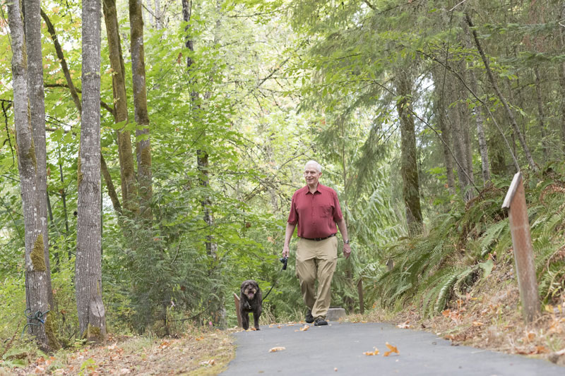 A senior man takes his dog for a walk in the park