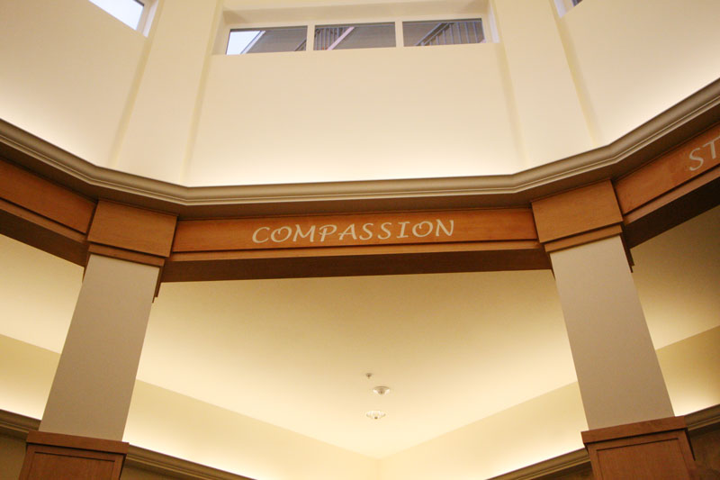 A photo of the word compassion written on the arches of a alcove