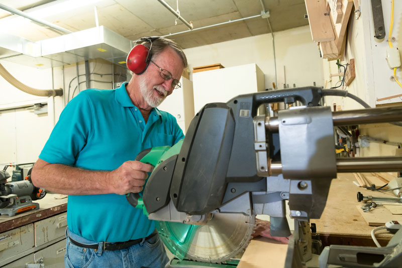 A senior man uses the saw at the woodworking shop at the Friendsview retirement community