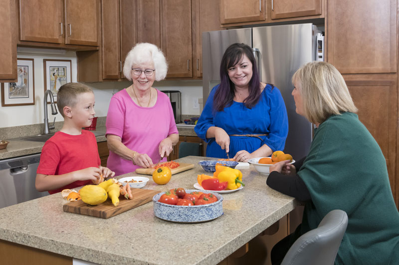 A senior woman makes a meal with her daughter and grandson