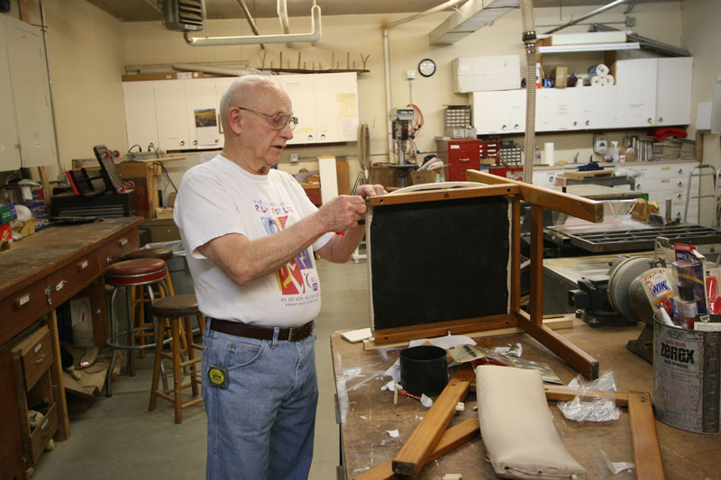 A senior man refurbishes a chair in the woodworking shop