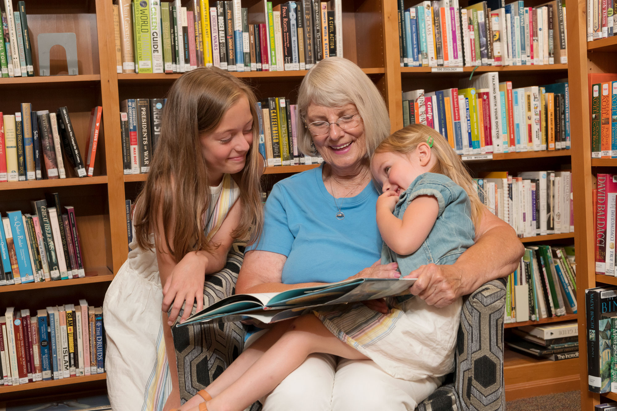 A senior woman sits in a chair in a library and reads a book to her two granddaughters