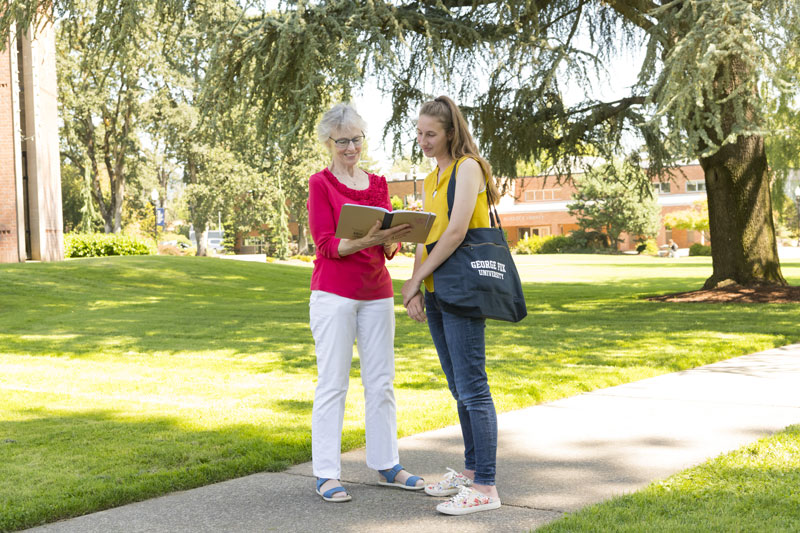 A senior woman stopping to talk a college student at George Fox University