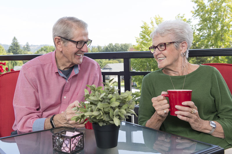 A senior couple sipping coffee on their deck