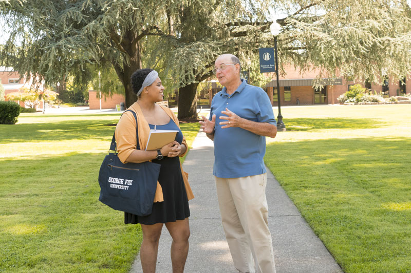A senior man stops to talk to a George Fox University