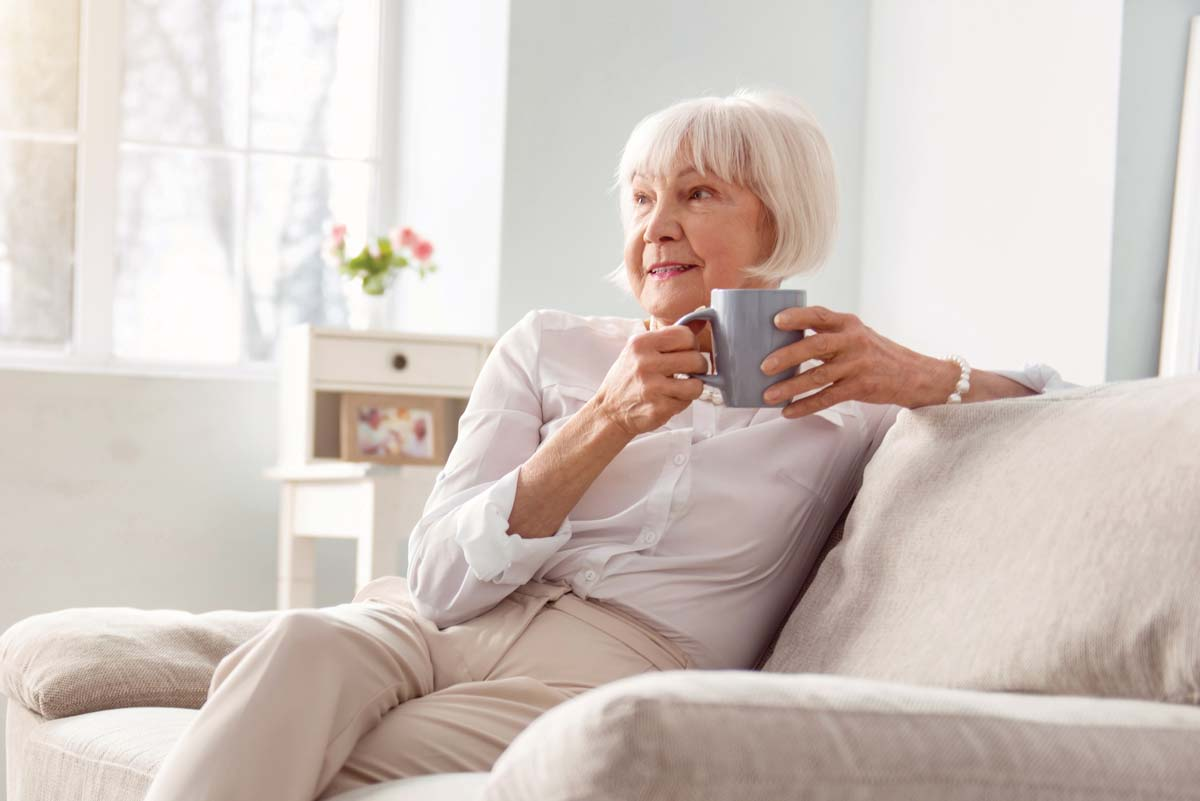 senior woman sips coffee in her quaker independent living apartment