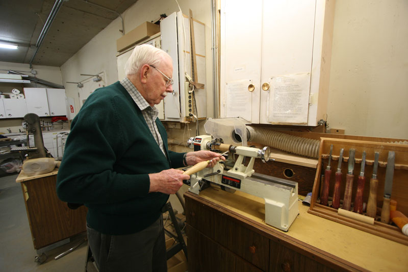 A senior man uses tools at the woodworking shop