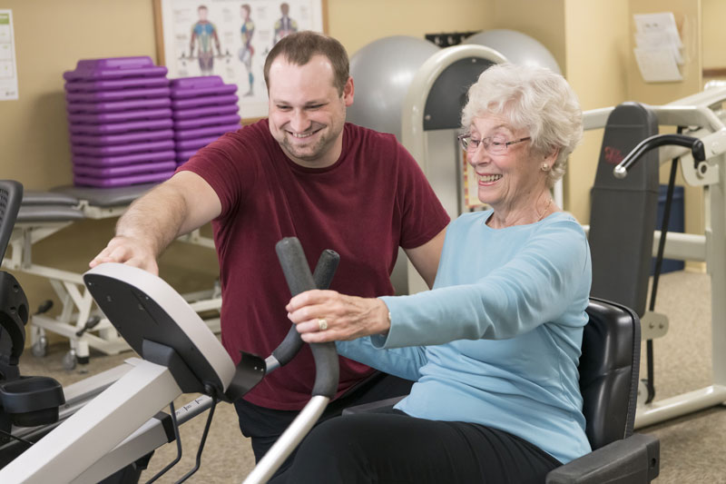 A senior woman works out with the help of a fitness coach or physical therapist