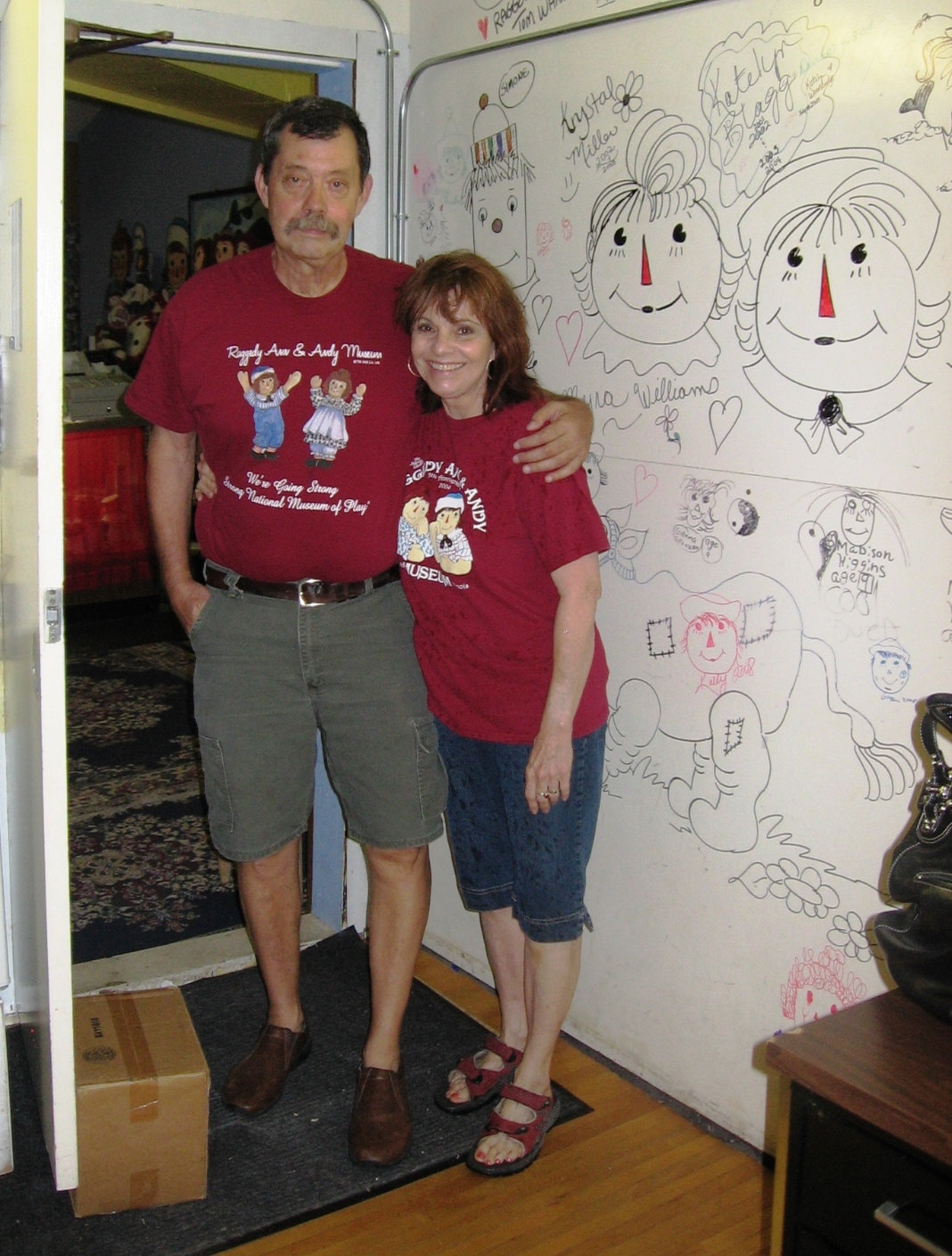 Our best friends in Arcola, Tom and Joni Wannamaker, pose by a wall of artwork inspired by Johnny Gruelle's illustrations.