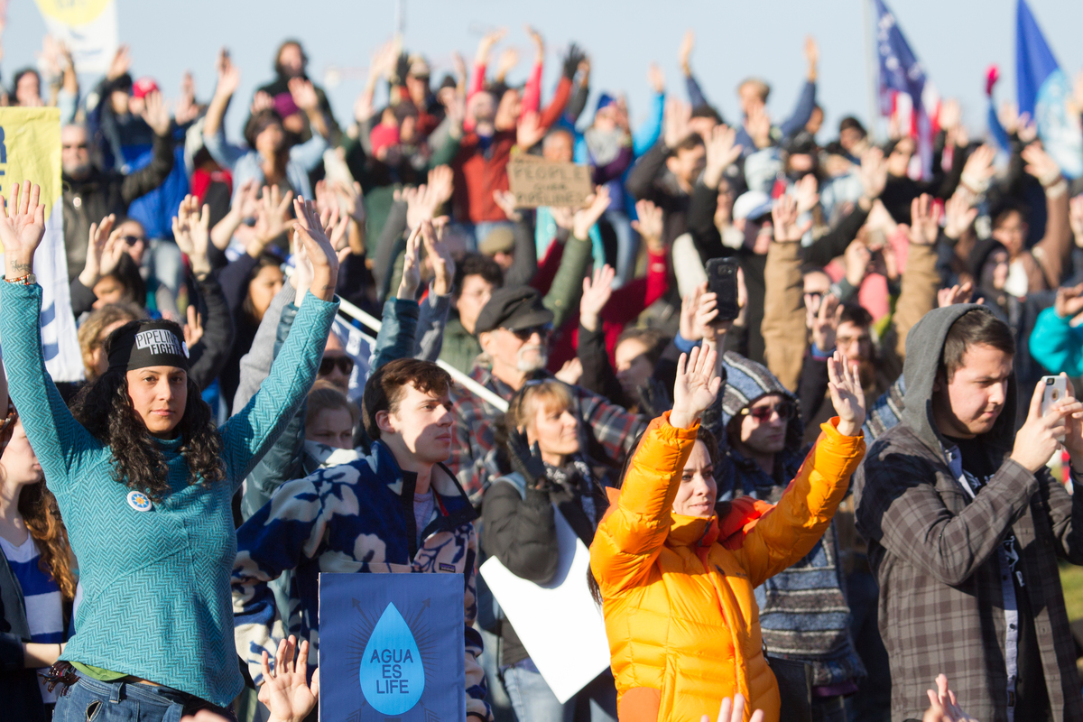 Standing Rock Nation supporters raise their arms in solidarity near the Washington Monument after marching from the Department of Justice calling for an end to militarized police abuse at the Oceti Sakowin water protectors camp near the reservation.