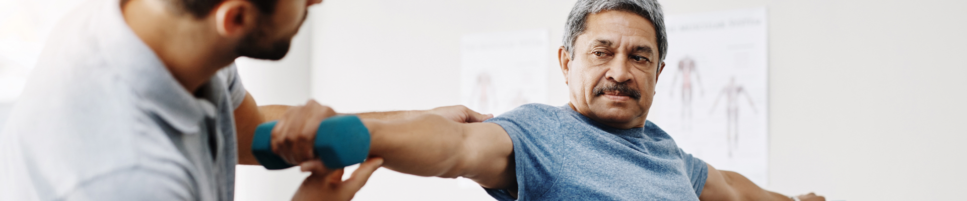 A senior man lifts a small hand weight as a part of his physical therapy treatment