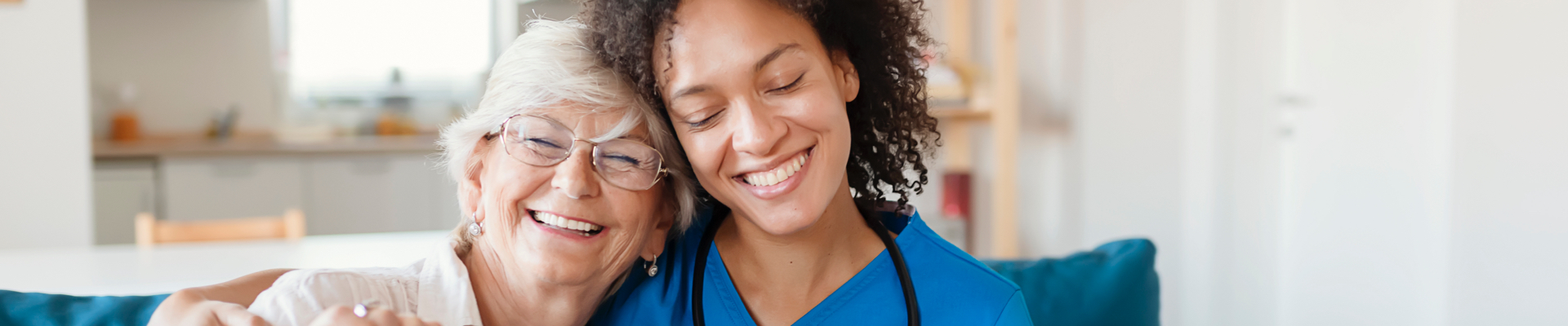 a health care professional and a senior woman sit side by side smiling and hugging