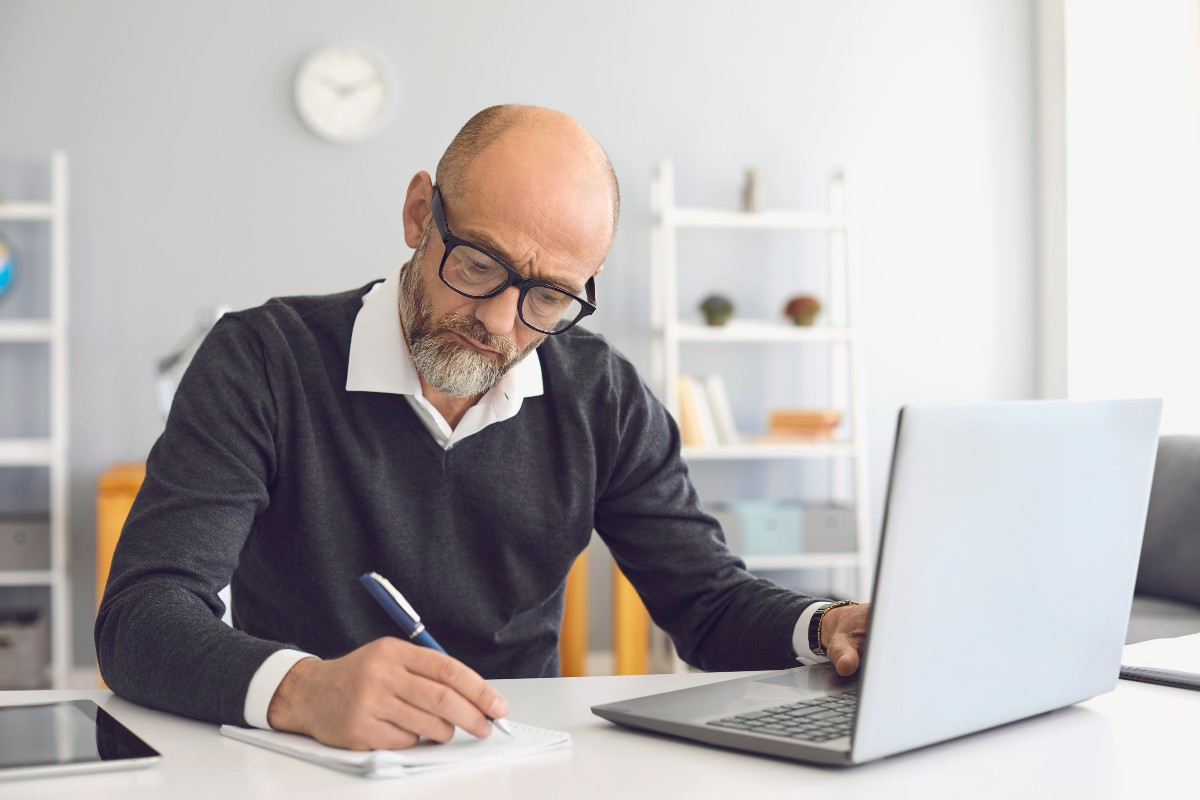 senior looking at a laptop and writing on a piece of paper sitting at a desk