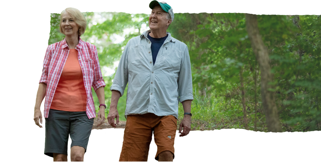A senior woman and senior man go hiking in the woods